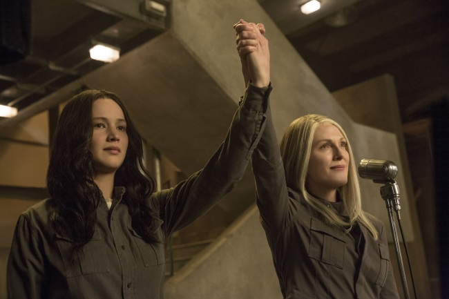 Katniss (Lawrence) and President Coin (Moore) speaking in front of District 13